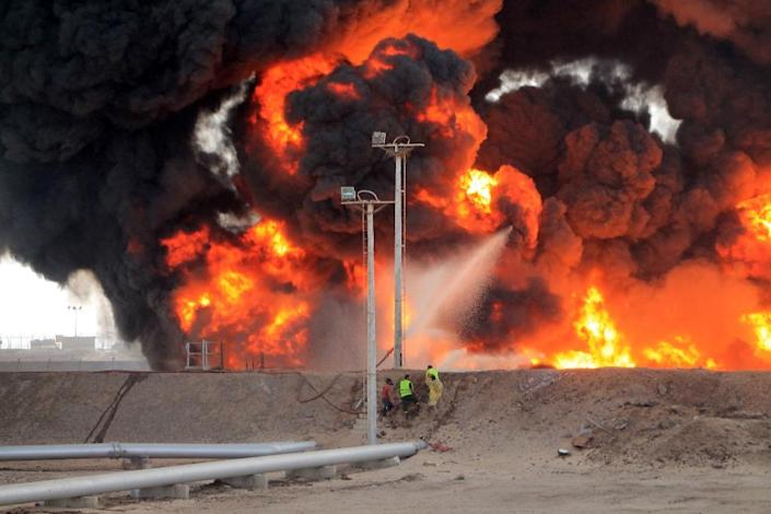 Yemeni fighters of the southern separatist movement and firefighters attempt to extinguish a blaze at an oil refinery in the port city of Aden on June 27, 2015, following shelling by Shiite Huthi rebels (AFP Photo/Sale Al-Obeidi)