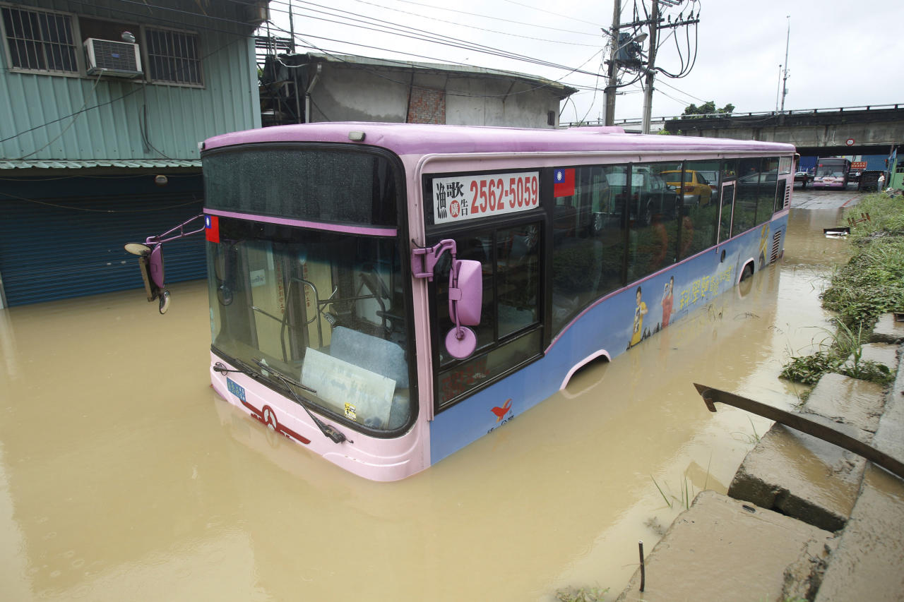A city bus sits in flood waters from approaching Typhoon Saola in suburban Taipei, Taiwan, Thursday, Aug. 2, 2012. The slow-moving typhoon spawning torrential rains slammed into eastern Taiwan early Thursday, flooding farmlands, disrupting transportation and turning the normally bustling capital of Taipei into a ghost town. (AP Photo/Wally Santana)