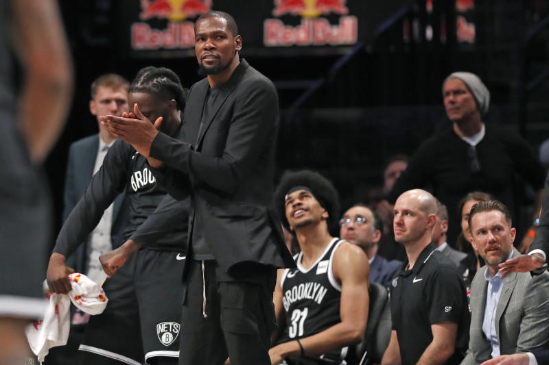 Injured Brooklyn Nets center Kevin Durant, who is recovering from an Achilles injury, stands and applauds this team's performance during the first half of an NBA basketball game against the New York Knicks, Friday, Oct. 25, 2019, in New York. Nets center Jarrett Allen (31) looks on. (AP Photo/Kathy Willens)