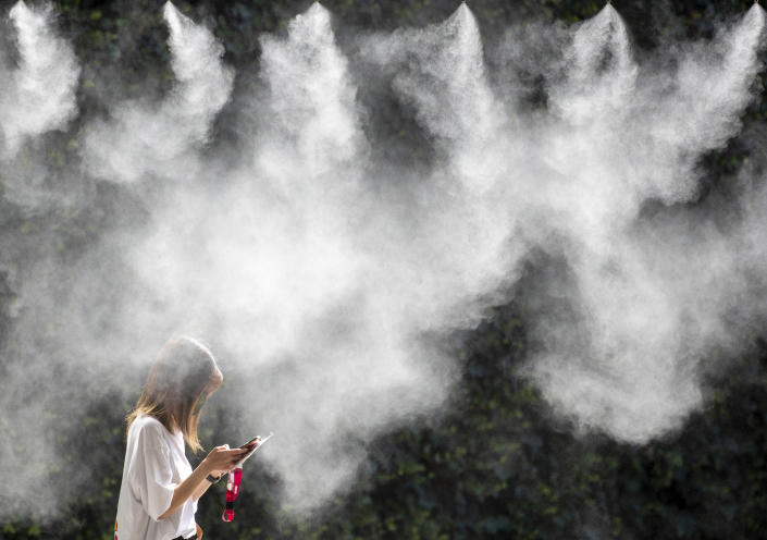 <p>An Olympic accredited media representative passes a spray of cooling water jets outside the Main Press Centre on a hot day in Tokyo at the Tokyo 2020 Olympic Games on July 20, 2021 in Tokyo, Japan. (Photo by Tim Clayton/Corbis via Getty Images)</p>