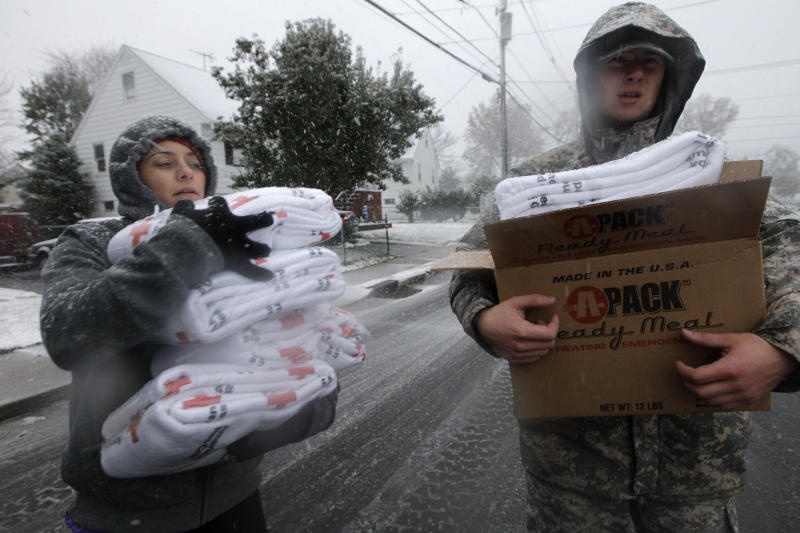 Volunteer Karina Ayubi, left, joins National Guardsman Brandon Kyle as they distribute blankets donated by the American Red Cross to residents without power as a Nor'easter approaches in the wake of Superstorm Sandy, Wednesday, Nov. 7, 2012, in Little Ferry. N.J. (AP Photo/Kathy Willens)