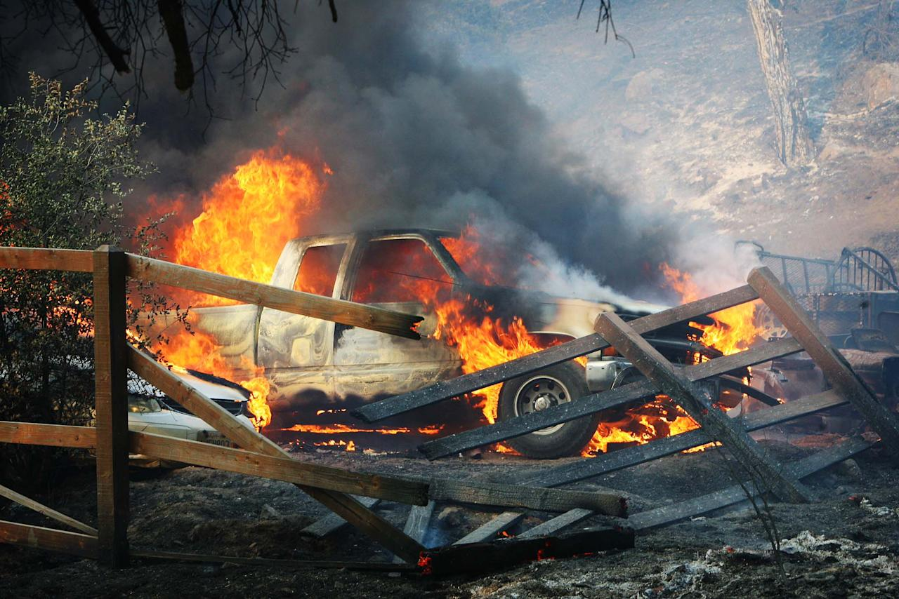A pickup truck is engulfed in flames as the Silver Fire roars through a residential area near Hwy 243 and Twin Pines Road between Banning and Idyllwild, Calif. on Wednesday, Aug. 7, 2013. (AP Photo/The Press-Enterprise, Frank Bellino)