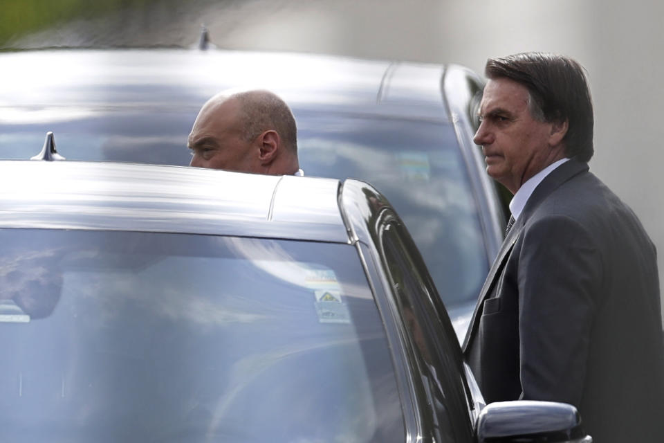 Photographed through a fence, Brazilian President Jair Bolsonaro gets into a car after talking to supporters as he leaves the presidential residence, Alvorada Palace, in Brasilia, Brazil, Friday, March 19, 2021. (AP Photo/Eraldo Peres)