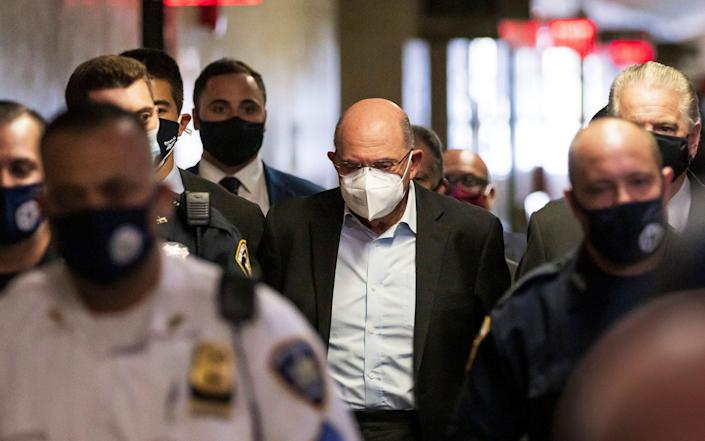 Allen Weisselberg (C), the chief financial officer for the Trump Organization, is escorted by police officers into a court hearing wearing handcuffs - Shutterstock