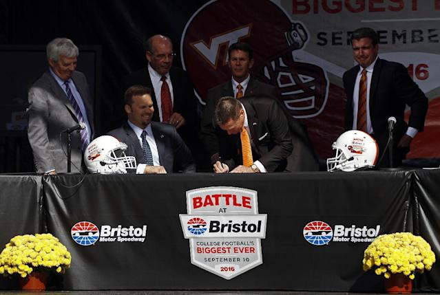 """Tennessee head football coach Butch Jones signs the contract as Marcus Smith, president of Speedway Motorsports, seated, Virginia Tech head football coach Frank Beamer, standing at left, Virginia Tech athletic director Jim Weaver, second from left, Tennessee athletic director Dave Hart, second from right, and Jerry Caldwell, general manager of Bristol Motor Speedway, right, watch during a press conference at Bristol Motor Speedway Monday, Oct. 14, 2013, in Bristol, Tenn. Tennessee and Virginia Tech will finally play a football game at Bristol Motor Speedway in what is being billed as the """"Battle of Bristol."""" (AP Photo/Wade Payne)"""