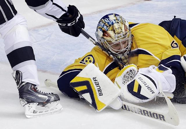 Nashville Predators goalie Pekka Rinne, of Finland, blocks a shot by Los Angeles Kings right wing Justin Williams, left, during the third period of an NHL hockey game Thursday, Oct. 17, 2013, in Nashville, Tenn. The Kings won 2-1 in a shootout. (AP Photo/Mark Humphrey)