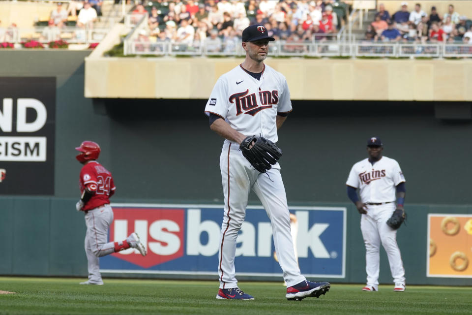 Minnesota Twins pitcher J.A. Happ, center, waits as Los Angeles Angels' Kurt Suzuki, left, rounds the bases on a two-run home run during the first inning of a baseball game, Friday, July 23, 2021, in Minneapolis. (AP Photo/Jim Mone)