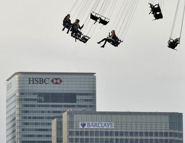 Financial offices of Canary Wharf are seen behind visitors to the O2 arena enjoying a fairground ride in east London