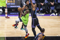 Minnesota Timberwolves forward Anthony Edwards (1) looks to pass the ball as he's defended by Sacramento Kings center Hassan Whiteside (20) during the first quarter of an NBA basketball game in Sacramento, Calif., Wednesday, April 21, 2021. (AP Photo/Hector Amezcua)