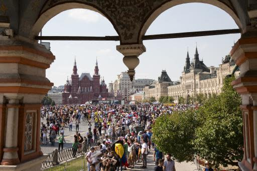 Soccer fans and tourists stroll around in Red Square with the Historical Museum, left, and the State Shop, GUM, right, in the background during the 2018 soccer World Cup in Moscow, Russia, Monday, June 18, 2018. (AP Photo/Alexander Zemlianichenko)