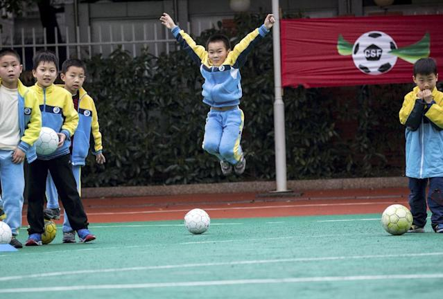 FILE - In this Wednesday, March 18, 2015 file photo, students take part in a soccer class at a primary school in Hangzhou in east China's Zhejiang province. With backing from the country's most powerful football fan, Chinese President Xi Jinping, the government is investing in the long-term development of the sport, recently unveiling a reform plan on March 16, 2015 to expand soccer programs at schools across the country. (AP Photo/File)