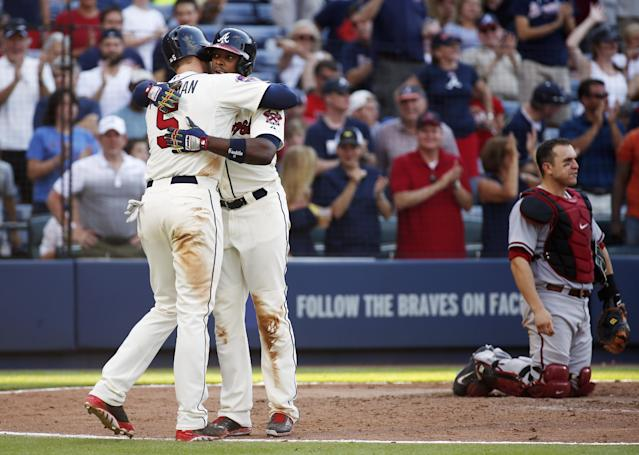 Atlanta Braves' Justin Upton hugs Freddie freeman (5) after hitting a two-run home run as Arizona Diamondbacks catcher Miguel Montero (26) looks on in the sixth inning of a baseball game in Atlanta, Saturday, July 5, 2014. (AP Photo/John Bazemore)