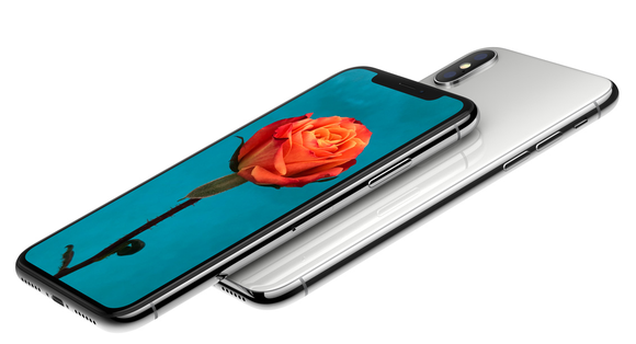 Two iPhone X devices. One is facedown, the other is displaying a picture of a rose.