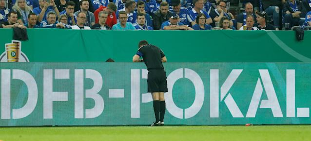 Soccer Football - DFB Cup - Schalke 04 vs Eintracht Frankfurt - Veltins-Arena, Gelsenkirchen, Germany - April 18, 2018 Referee Robert Hartmann checks with the Video Assistant Referee (VAR) before ruling a goal out for offside REUTERS/Leon Kuegeler DFB RULES PROHIBIT USE IN MMS SERVICES VIA HANDHELD DEVICES UNTIL TWO HOURS AFTER A MATCH AND ANY USAGE ON INTERNET OR ONLINE MEDIA SIMULATING VIDEO FOOTAGE DURING THE MATCH.
