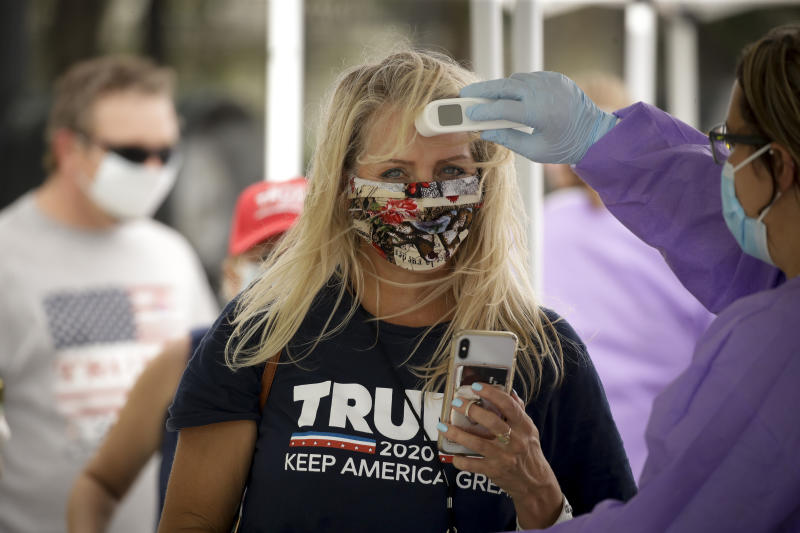 A Trump supporter gets her temperature checked