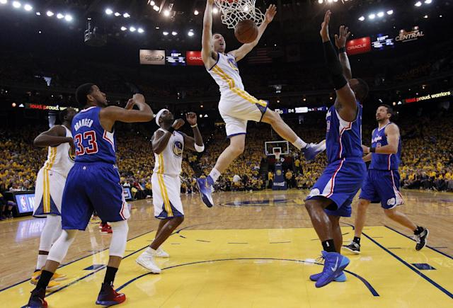 Golden State Warriors' Klay Thompson, center, dunks against the Los Angeles Clippers during the first half in Game 4 of an opening-round NBA basketball playoff series on Sunday, April 27, 2014, in Oakland, Calif. (AP Photo/Marcio Jose Sanchez)