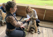 """This image released by National Geographic shows Mariana van Zeller, background, with a tiger cub as the animal if fed by a handler at Myrtle Beach Safari during van Zeller's """"Trafficked with Mariana van Zeller"""" series. The episode airs Wednesday on National Geographic channel. (National Geographic via AP)"""