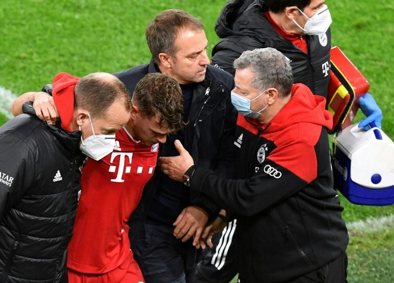 Bayern Munich head coach Hansi Flick (2R) helps Joshua Kimmich (2L) after the Germany star was injured in the 3-2 win at Dormtund a fortnight ago