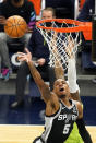 San Antonio Spurs' Dejounte Murray (5) lays up a shot against the Minnesota Timberwolves in the first half of an NBA basketball game Saturday, Jan. 9, 2021, in Minneapolis. (AP Photo/Jim Mone)
