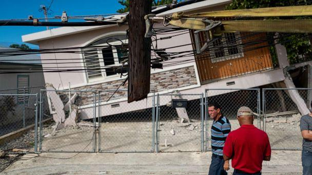 PHOTO: People pass by a house damaged by a 5.8 earthquake in Guanica, Puerto Rico on January 6, 2020. (Ricardo Arduengo/AFP via Getty Images)