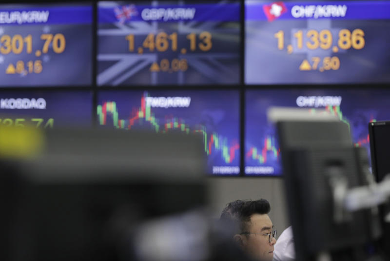 A currency trader watches the computer monitors near the screens the foreign exchange rates at the foreign exchange dealing room in Seoul, South Korea, Tuesday, Oct. 23, 2018. Asian stocks slid on Tuesday as worries about softening Chinese growth rattled investors, following a rally that was not picked up by Wall Street overnight. (AP Photo/Lee Jin-man)