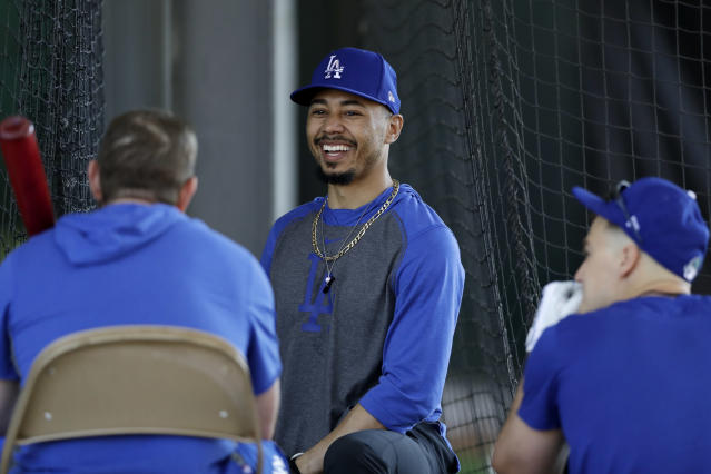 Los Angeles Dodgers outfielder Mookie Betts, center, talks with second baseman Max Muncy, left, and right fielder Joc Pederson, right, during spring training baseball Monday, Feb. 17, 2020, in Phoenix. (AP Photo/Gregory Bull)