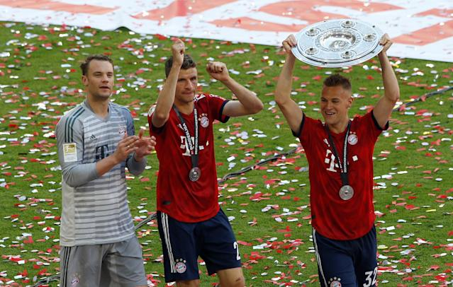 Soccer Football - Bundesliga - Bayern Munich v VfB Stuttgart - Allianz Arena, Munich, Germany - May 12, 2018 Bayern Munich's Joshua Kimmich celebrates winning the Bundesliga with the trophy alongside Manuel Neuer and Thomas Mueller REUTERS/Michaela Rehle DFL RULES TO LIMIT THE ONLINE USAGE DURING MATCH TIME TO 15 PICTURES PER GAME. IMAGE SEQUENCES TO SIMULATE VIDEO IS NOT ALLOWED AT ANY TIME. FOR FURTHER QUERIES PLEASE CONTACT DFL DIRECTLY AT + 49 69 650050