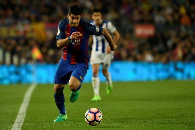 Barcelona's Luis Suarez runs with the ball during their match against Real Sociedad at the Camp Nou stadium in Barcelona on April 15, 2017