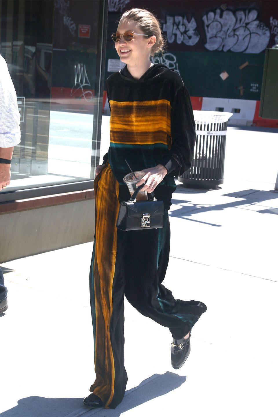 <p>In a striped velour tracksuit, circular shades, Andre Assous shoes and carrying a STALVEY mini top handle bag while out in NYC. </p>