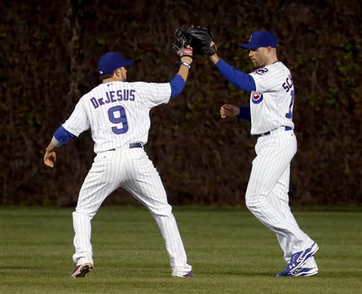 Chicago Cubs center fielder David DeJesus, left, and right fielder Nate Schierholtz celebrate their 2-1 win over the St. Louis Cardinals after a baseball game Tuesday, May 7, 2013, in Chicago. (AP Photo/Charles Rex Arbogast)