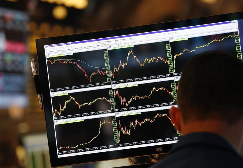 A screen displays stock charts while a trader works at his post on the floor at the New York Stock Exchange