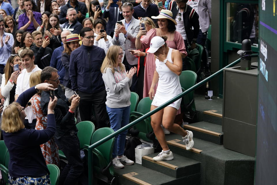 Australia's Ashleigh Barty walks back down the stands after climbing it to meet her team, at the end of her match against Czech Republic's Karolina Pliskova on day twelve of the Wimbledon Tennis Championships in London, Saturday, July 10, 2021. (AP Photo/Alberto Pezzali)