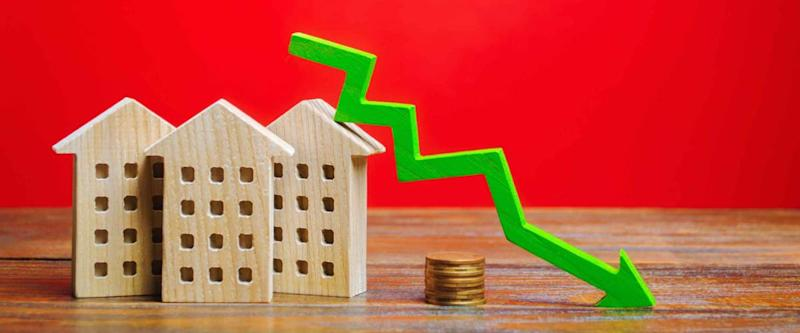 Miniature wooden houses and a green arrow down. The concept of falling mortgage rates.