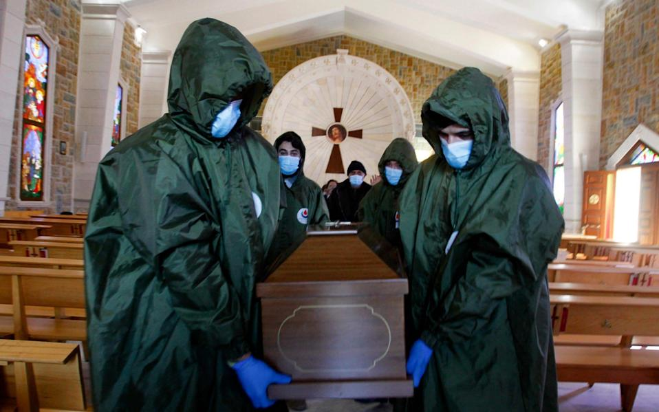 Members of Lebanon's Shiite Hezbollah movement's Islamic health unit, transport the coffin of a Lebanese Christian woman who died of the Covid-19 out of a church to be inhumated in a nearby cemetary - Mahmoud ZAYYAT / AFP