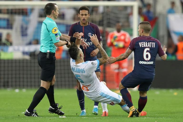 Marseille forward Lucas Ocampos (C) falls after an altercation with Paris Saint-Germain forward Neymar (C, top) during the French L1 at the Velodrome Stadium in Marseille, France on October 22, 2017