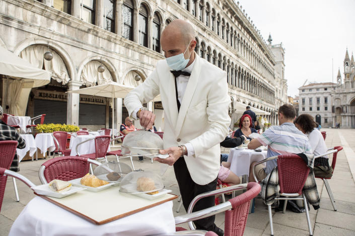 A waiter works in St. Mark's Square in Venice, northern Italy, Saturday, May 1, 2021. Italy is gradually reopening after six months of rotating virus closures allowing outdoor dining. (Filippo Ciappi/LaPresse via AP)