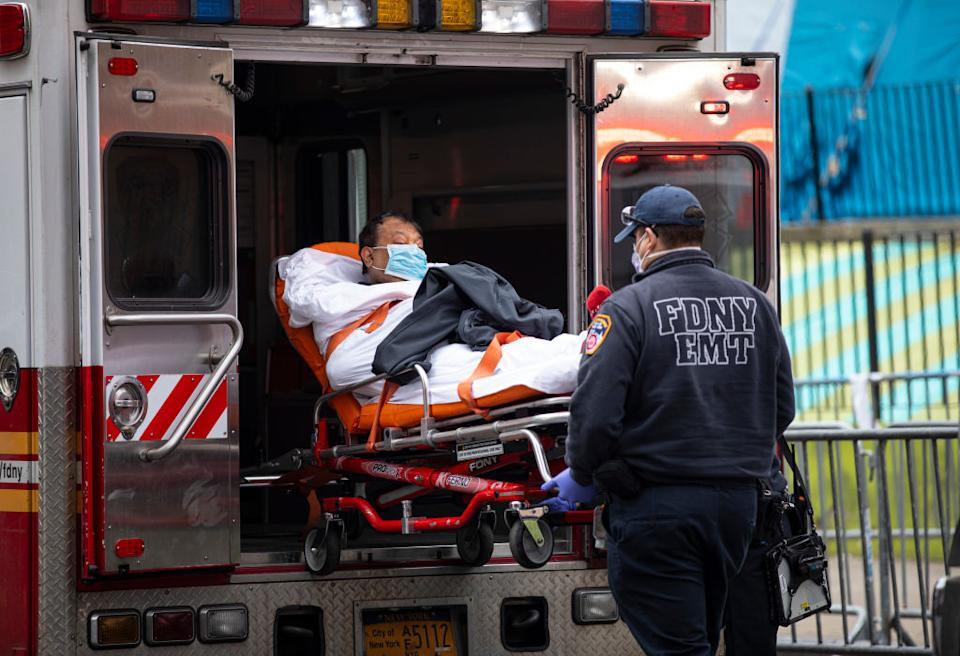 Two members of the Fire Department of New York Emergency Medical Team wheel in a patient with potentially fatal coronavirus to the Elmhurst Hospital Center in the Queens borough of New York City.