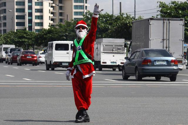 Ramiro Hinojas, a Pasay traffic enforcer wearing a Santa Claus costume dances while controlling the traffic along Diosdado Macapagal Avenue in Pasay City, south of Manila. Hinojas, 54 years old, has been a traffic enforcer for six years. According to Hinojas, this was his way of entertaining the motorist this Christmas season despite heavy traffic in the busy street. (Marlo Cueto/NPPA Images)