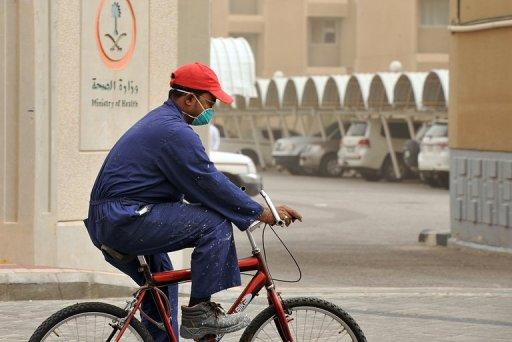 A foreign worker wears a mask as he rides a bicycle near the King Fahad hospital in the city of Hofuf on June 16, 2013