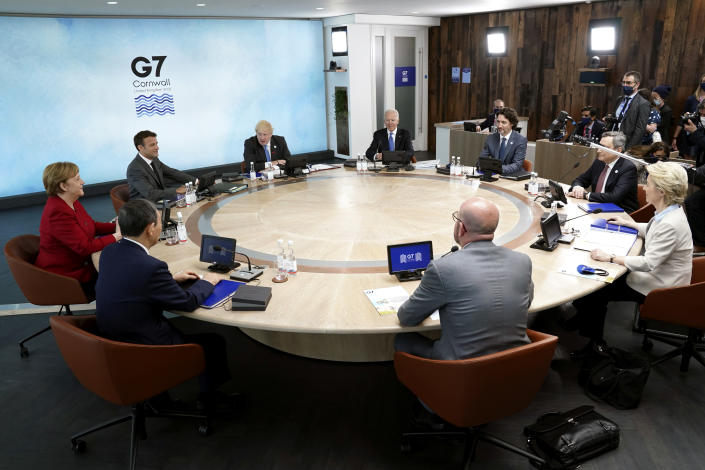 Clockwise from left, German Chancellor Angela Merkel and French President Emmanuel Macron, British Prime Minister Boris Johnson, U.S. President Joe Biden, Canadian Prime Minister Justin Trudeau, Italy's Prime Minister Mario Draghi, European Commission President Ursula von der Leyen, European Council President Charles Michel, and Japan's Prime Minister Yoshihide Suga sit around a table during the G-7 summit at the Carbis Bay Hotel in Carbis Bay, St. Ives, Cornwall, England, Friday, June 11, 2021. Leaders of the G-7 begin their first of three days of meetings on Friday, in which they will discuss COVID-19, climate, foreign policy and the economy. (Kevin Lamarque/Pool via AP)
