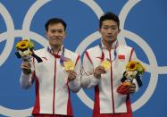 Wang Zongyuan and Xie Siyi of China pose for photo after winning gold medals during the men's Synchronized 3m Springboard Final at the Tokyo Aquatics Centre at the 2020 Summer Olympics, Wednesday, July 28, 2021, in Tokyo, Japan. (AP Photo/Dmitri Lovetsky)