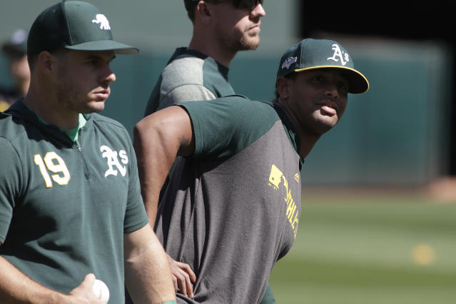 Oakland Athletics' Josh Phegley (19) and Khris Davis, right, warm up during baseball practice in Oakland, Calif., Tuesday, Oct. 1, 2019. The Athletics are scheduled to face the Tampa Bay Rays in an American League wild-card game Wednesday, Oct. 2. (AP Photo/Jeff Chiu)