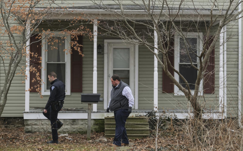 Law enforcement officers walk around a vacant house in Port Clinton, Ohio where the body of Harley Dilly, 14, was found inside the chimney. Source: Jeremy Wadsworth/The Blade via AP