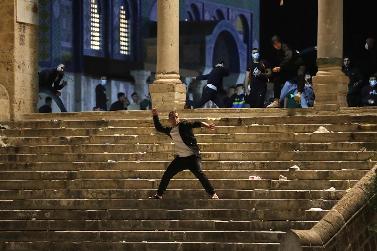 A Palestinian hurls stones at Israeli police during clashes at the compound that houses Al-Aqsa Mosque, known to Muslims as Noble Sanctuary and to Jews as Temple Mount, amid tension over the possible eviction of several Palestinian families from homes on land claimed by Jewish settlers in the Sheikh Jarrah neighbourhood, in Jerusalem's Old City, May 7, 2021. (Ammar Awad/Reuters)