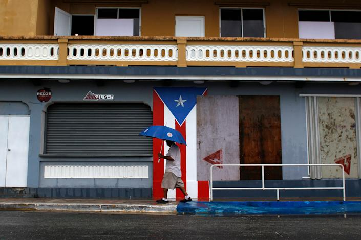 A man with an umbrella walks on a sidewalk as Hurricane Irma approaches Puerto Rico in Luquillo, on September 6, 2017. Irma is expected to reach the Virgin Islands and Puerto Rico by nightfall on September 6. / AFP PHOTO / Ricardo ARDUENGO (Photo credit should read RICARDO ARDUENGO/AFP/Getty Images)