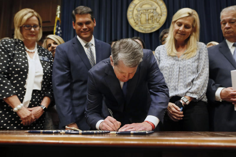 FILE - In this May 7, 2019, file photo, Georgia's Republican Gov. Brian Kemp, center, signs legislation in Atlanta, banning abortions once a fetal heartbeat can be detected, which can be as early as six weeks before many women know they're pregnant. Georgia became the fourth state to enact the ban on abortions after a fetal heartbeat can be detected. (Bob Andres/Atlanta Journal-Constitution via AP, File)