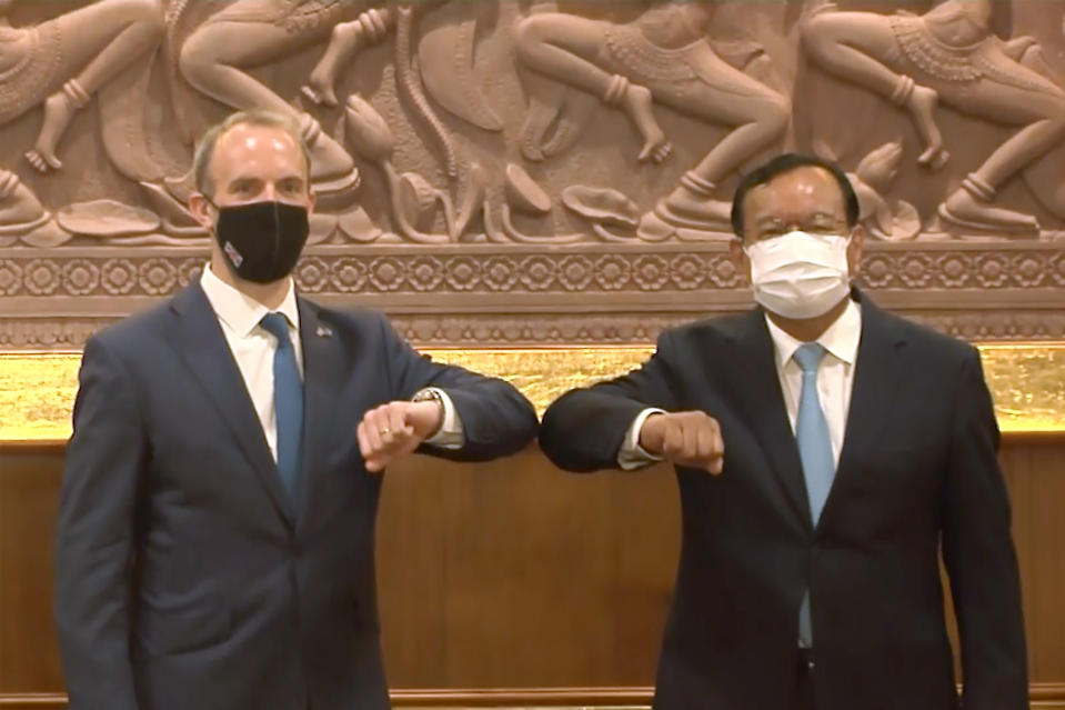 In this image made from video, Britain Foreign Secretary Dominic Raab, left, and Cambodia Foreign Minister Prak Sokhonn greet each other while social distancing to curb the spread of the coronavirus at the Foreign Ministry, Wednesday, June 23, 2021, in Phnom Penh, Cambodia. (AP Photo)