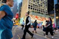 FILE PHOTO: People cross a street the Central business district in Hong Kong