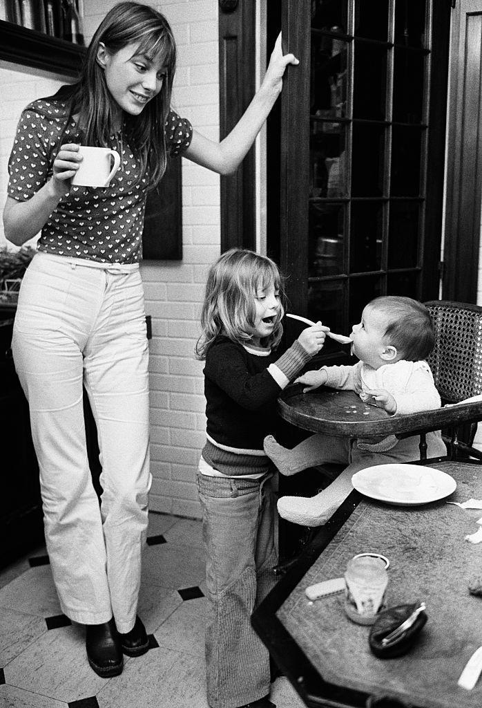 <p>The English model enjoys a cup of coffee while her daughter, Kate Barry, helps feed her newborn baby, Charlotte Gainsbourg. </p>
