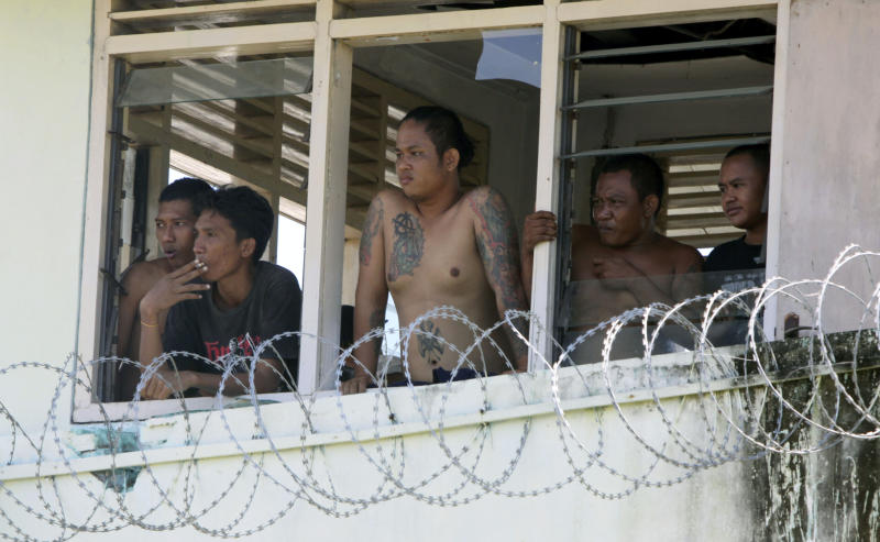 Indonesian inmates look out the window of a prison tower at the Kerobokan jail in Denpasar, Bali, Indonesia, Thursday, Feb. 23, 2012. Indonesia started moving foreigners and a handful of other inmates from the overcrowded prison on Bali island Thursday after two days of rioting, officials said, as troops backed by water canons and armored vehicles surrounded the tense facility. (AP Photo/Firdia Lisnawati)